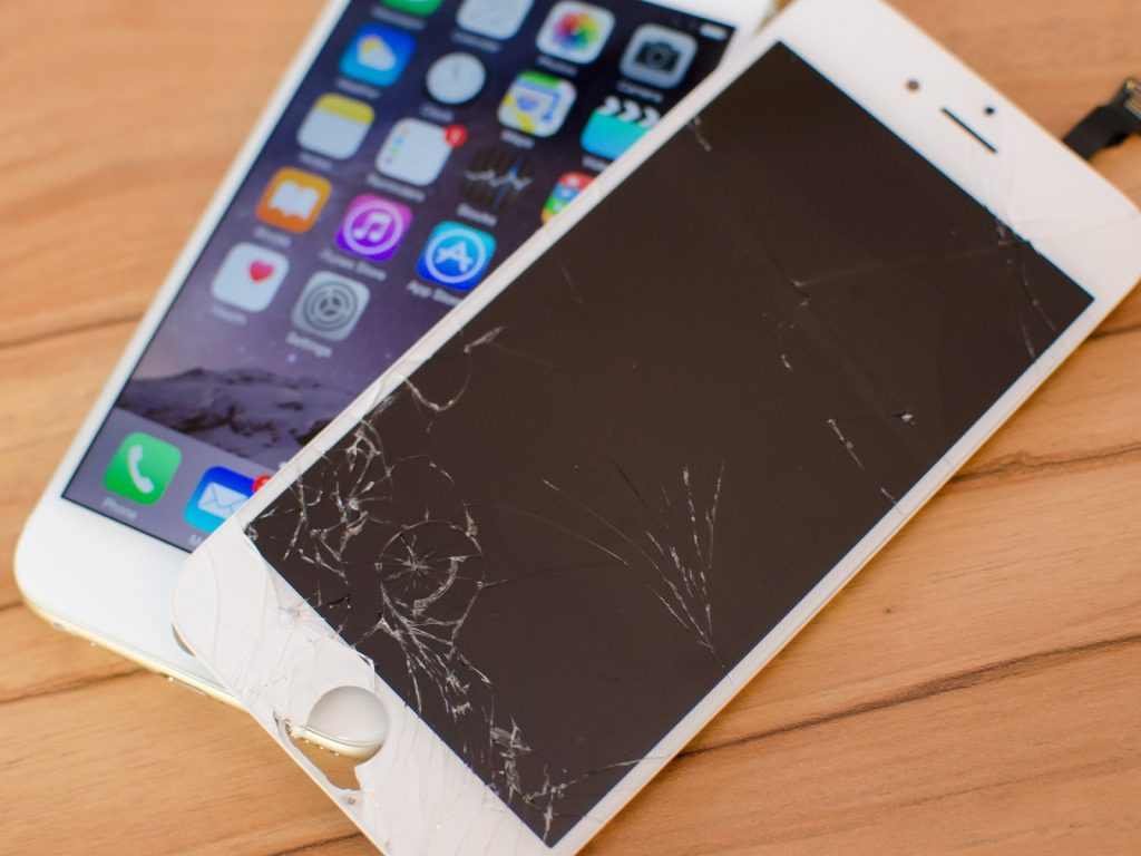 iPhone 6 with a broken screen, laying on top of a new iPhone 6
