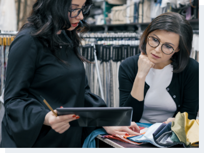 A female retail employee and a customer looking up information on a product on an iPad