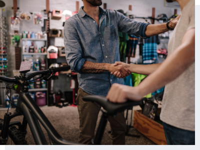 A bicycle shop owner shaking hands with a male customer who just purchased a bike