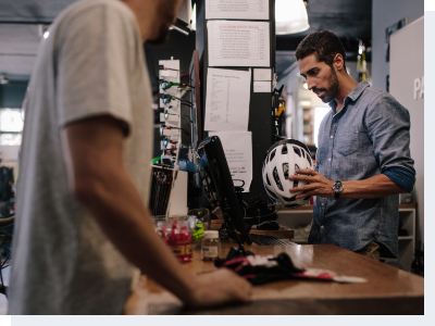 A cashier standing the cash register looking up information on a cycling helmet for the male customer at the register with him