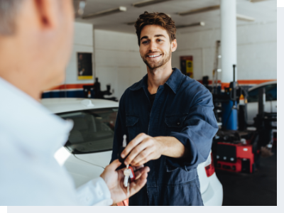 A mechanic handing keys to the owner of the car