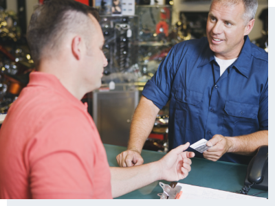 two man standing at the counter of a repair shop and making a transaction
