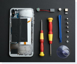 opened iPhone with tools lying beside it